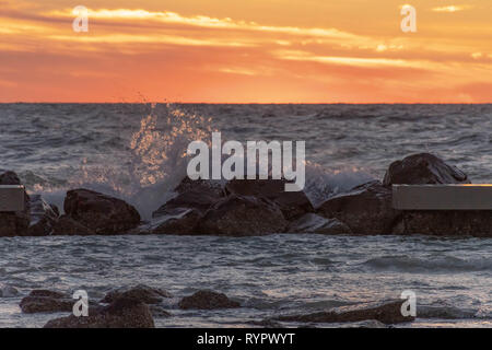 Stunning pink sky as the waves crash on the rocks in the Gulf of Mexico - Stock Photo
