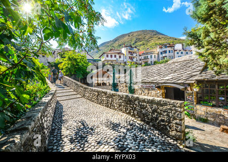 Tourists walk a narrow cobblestone path over a bridge and past a cafe in the medieval city of Mostar, Bosnia on an autumn morning. - Stock Photo
