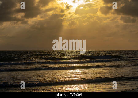 Sunset beach in Florida on the Gulf of Mexico with a bright sky with light shining through the clouds - Stock Photo