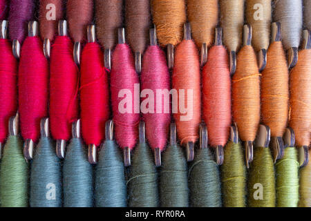 Image of three rows of colorful bobbin threads, stitching or sewing of red, orange, brown and other colors - Stock Photo