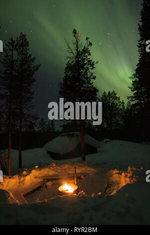 Fireplace with a wooden cottage and trees covered in snow behind and aurora borealis (northern light) above on a winter night in Finnish Lapland. Saar - Stock Photo