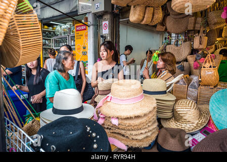 Bangkok, Thailand - May 13, 2018: three women talk to each other behind a shop counter filled with hats and wicker bags at Chatuchak Weekend Market. - Stock Photo