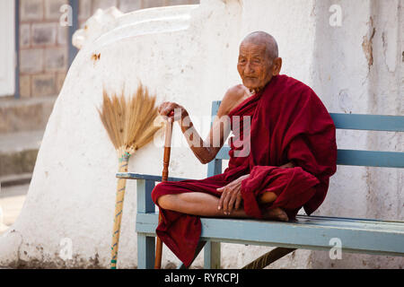 An old Buddhist monk sits on a bench at Shwe Yan Pyay monastery near Kalaw, Myanmar - Stock Photo