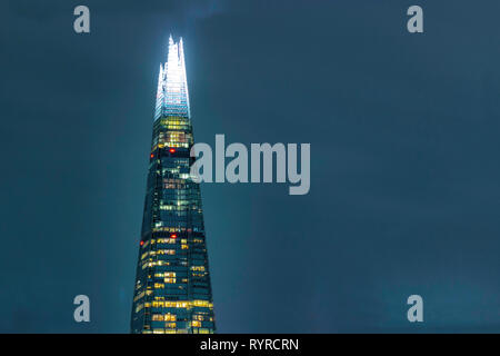 The Shard, London, England, March 14 2019. An isolated shot of the famous skyscraper illuminated against the night sky. - Stock Photo