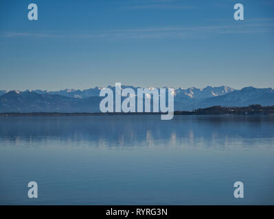 The snow-covered mountains are reflected in the calm water of Lake Starnberg. - Stock Photo