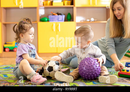 little children girl and boy playing with balls in nursery - Stock Photo