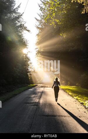 Young woman jogging on a street, sunlight shines through trees, Oregon Coast Highway, Oregon, USA - Stock Photo