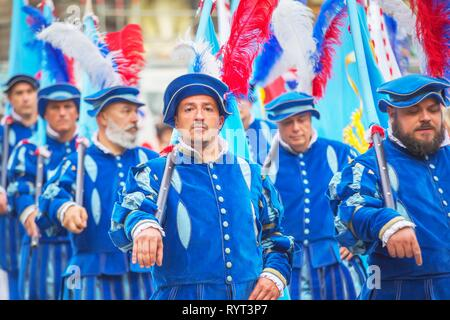 Participants in Calcio Storico Fiorentino festival marching through the city center in historical costumes, Florence, Tuscany - Stock Photo