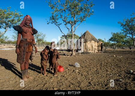 Himba woman with her children in village, Sesriem, Kaokoland, Namibia - Stock Photo