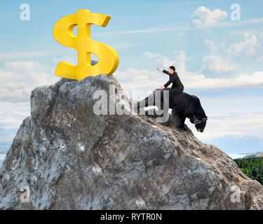 Businessman riding black bear pursuing gold dollar sign on mountain peak with sky clouds background. Fight back bearish market concept. - Stock Photo
