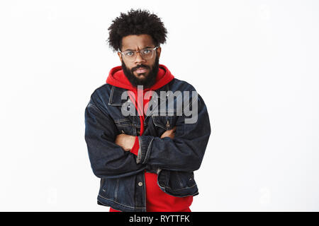 Portrait of annoyed and angry handsome african-american stylish bearded man with glasses and pierced nose frowning crossing arms over chest in - Stock Photo