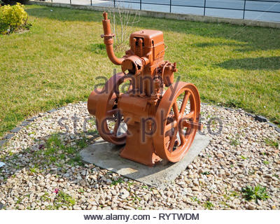 Old vintage 4 Stroke Stationary Engine painted and used as a decorative object in a garden,surrounded with pebbles - Stock Photo