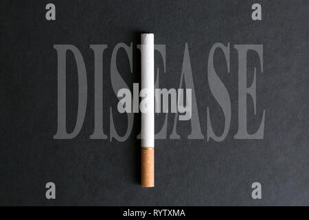 Cigarette tobacco makes up the word illness on a black background. - Stock Photo