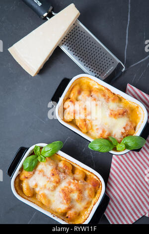 Gnocchi alla sorrentina in two pasta bake dishes on a dark kitchen top and pamesan cheese and a grater in the background. Baked gourmet gnocchi with m - Stock Photo