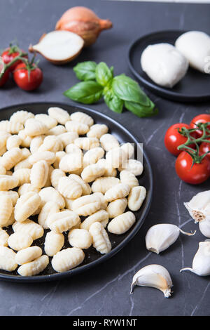 Fresh Italian ingredients. Baked gnocchi alla sorrentina ingredients. Fresh gnocchi on a black plate with fresh Italian products in the background. Gr - Stock Photo