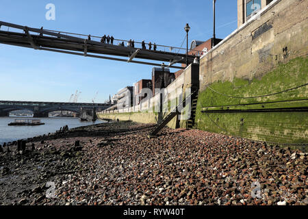 View of people standing on Millennium Bridge & algae covered river wall on north bank of River Thames at low tide in London England UK  KATHY DEWITT - Stock Photo