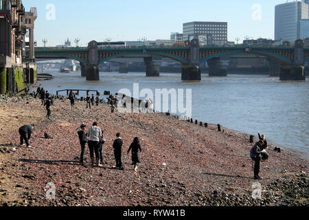 View of River Thames at low tide, school children mudlarking near Queenhithe and Southwark Brige in London EC4 England UK  KATHY DEWITT - Stock Photo
