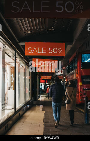 London, UK - March 9, 2019: People walking under sale signs on House of Fraser Oxford Street store, London. HoF is a British department store group wi - Stock Photo