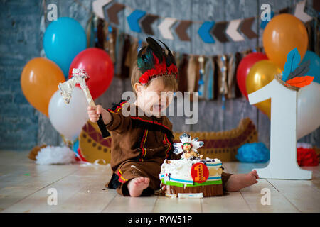 Photo shoot smash the cake for 1 year in the style of Indian chief. Little emotional boy with a tomahawk in costume of Apache and in feather headdress - Stock Photo