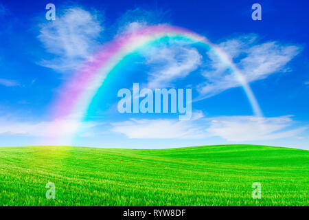 Idyllic landscape, rainbow over rolling green fields, in the background blue sky and white clouds - Stock Photo