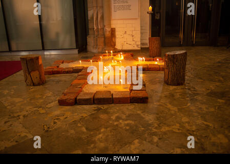 Candles burn  in a cross filled with sand in the St. Petri church - Stock Photo