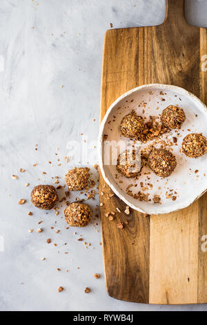 Bliss balls in a round handmade bowl on a wooden board