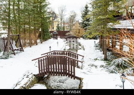 Winter scenery in the city, snow covered terrain visible two small bridges over a mountain stream and green coniferous trees. - Stock Photo