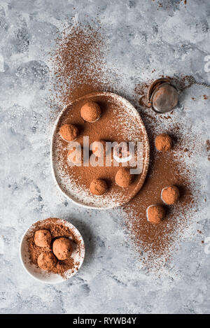Raw chocolate bliss balls dusted with cacao on an irregular shaped white plate - Stock Photo