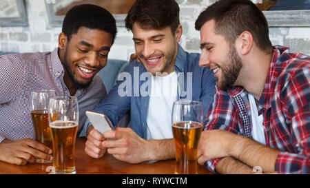 Friends meeting in bar, using smartphone and drinking beer - Stock Photo