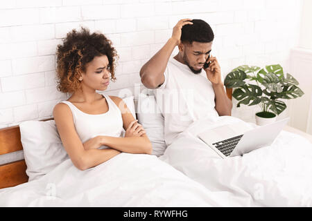 African-american guy working in bed and ignoring his wife - Stock Photo