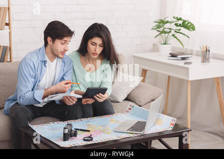 Couple counting finances for vacation, planning journey