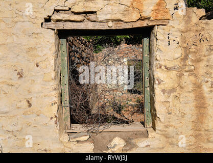 Central empty green window frame on rocky wall of abandoned house.  Through frame see barbed wires and rest of structure in ruin - Stock Photo