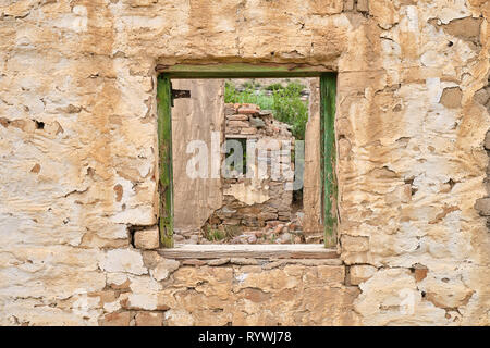 Central empty green window frame on rocky wall of abandoned house.  Through frame see crumbled walls of remaining ruined house - Stock Photo