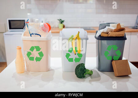 Waste sorting at home. Protect the environment. Colorful garbage bins with recycling icon full of plastic, food, paper on the table close-up - Stock Photo