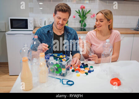 Protect the environment. Aware young couple recycling empty plastic bottles and lids while sitting at the table with other waste at home - Stock Photo