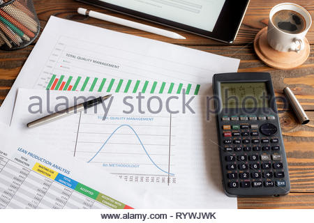Total Quality Management, Lean Production Analysis and Six Sigma Methodology Graphics on Work Desk - Stock Photo