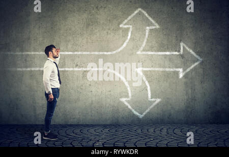 Confident businessman looking into the future as a crossroad arrows split in three different ways. Choosing the right way making difficult decision co - Stock Photo