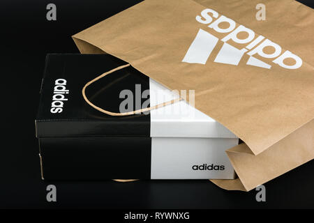 BURGAS, BULGARIA - MARCH 8, 2019: Paper bag with original Adidas logo and Adidas shoes box on black background. - Stock Photo