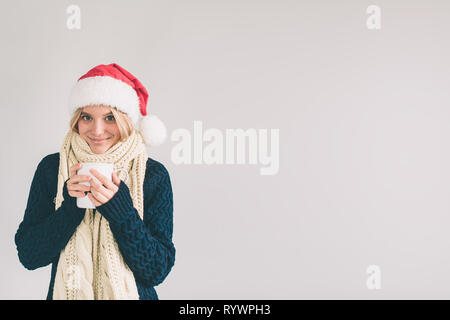Smiling woman in Santa hat with cup of coffee, isolated on white. The girl is dressed in sweater, christmas cap and scarf studio shot . - Stock Photo