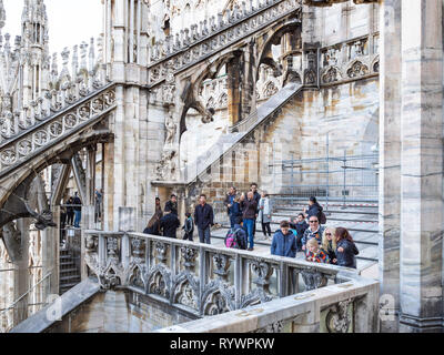 MILAN, ITALY - FEBRUARY 24, 2019: tourists walk on roof of Milan Cathedral (Duomo di Milano) in Milan in morning. This Basilica is the largest church  - Stock Photo