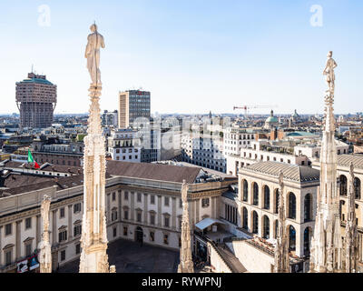 MILAN, ITALY - FEBRUARY 24, 2019: statues on spires of roof of Milan Cathedral (Duomo di Milano) over Royal Palace (Palazzo Reale) and Milan city. Thi - Stock Photo