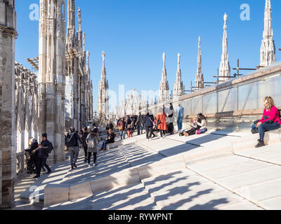MILAN, ITALY - FEBRUARY 24, 2019: many tourists on roof of Milan Cathedral (Duomo di Milano) in Milan in morning. This Basilica is the largest church  - Stock Photo