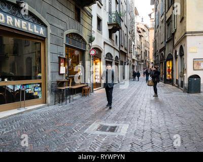 BERGAMO, ITALY - FEBRUARY 25, 2019: people walk on street via Gombito in Citta Alta (Upper Town) of Bergamo city, Lombardy in evening - Stock Photo