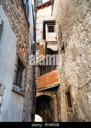 Travel to Italy - shabby old apartment houses over narrow medieval side street in Upper Town (Citta Alta) of Bergamo city, Lombardy - Stock Photo