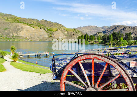 CROMWELL, NEW ZEALAND - OCTOBER 21 2019;  Group four youth sitting socializing  on end of pier on Lake Dunstan old cart with red wooden spoked wheel f - Stock Photo