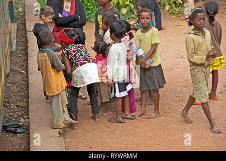 Local kids talking to young tourist children on the train station. The train Finarantsoa to Manakara. Madagascar. - Stock Photo