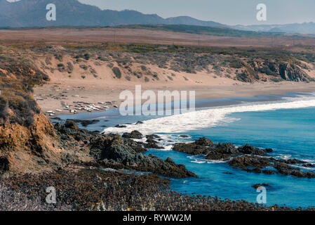 White ocean waves rolling onto sandy shoreline and beach below. - Stock Photo