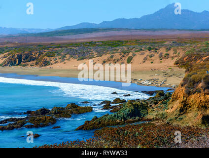 White waves rolling onto shore below, sandy beach and rocky coastline under bright blue sky. - Stock Photo