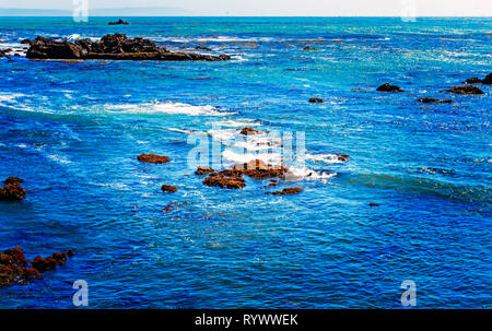 Rocks in the sea with waves crashing onto the rocks. - Stock Photo