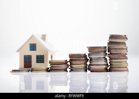 Increasing Coins Arranged In Front Of House Model Over White Desk